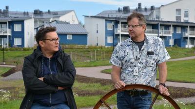 Jarkko Lyytinen och Kari Ojamies står i en park och diskuterar. Blåa hus i bakgrunden.