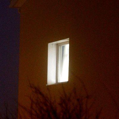 Valo palaa omakotitalon ikkunassa.
