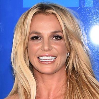 Britney Spears poserar och ler på röda mattan. Hon är klädd i en svart klänning.