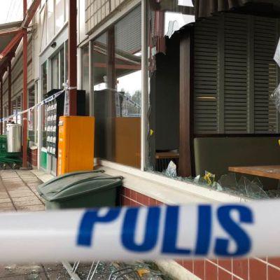 Joensuun Prisman rikottu näyteikkuna ja poliisin eristenauhaa etualalla.