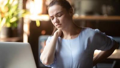 Kvinna sitter framför laptop, blundar, grimaserar och håller handen mot sin nacke