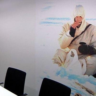 Seinällä iso kuva lumipukuisesta varusmiehestä maastossa.