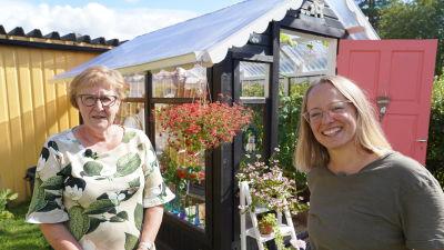 Två kvinnor som står framför ett litet växthus i en blommande trädgård.