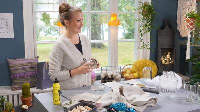 Lee står i hobbyrummet på Strömsö vid bordet med allt material som behövs för att göra sytillbehörsburkar.