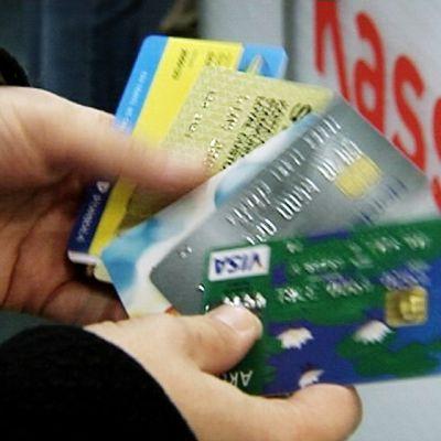 Luotto- ja bonuskortteja kädessä.