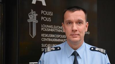 En polis i uniform står utanför polishuset i Åbo.