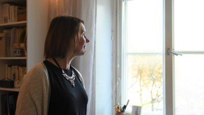 En kvinna tittar ut genom ett fönster.
