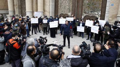 En man står i en folksamling och skriker med fingret i luften. Han omges av demonstranter bakom sig och fotografer framför sig.