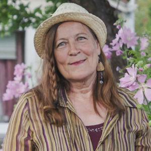 Kvinna i randig skjorta, stora örhängen och halmhatt står i trädgård med rosafärgade blommor omkring sig.