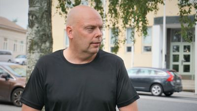 Man i svart t-skjorta står vid en väg.