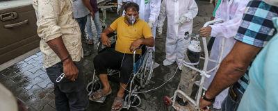 En indisk man i rullstol får extra syre utanför ett sjukhus i Ahmedaba,