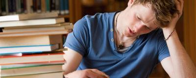 Man läser bok vid ett bord i ett bibliotek. I bildens vänstermiljö syns en trave böcker.