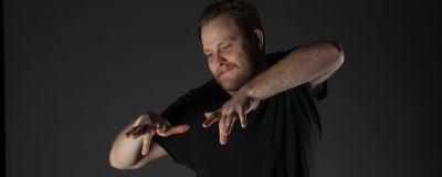 Jonas spelar luftpiano med armarna i en mörklagd studio.