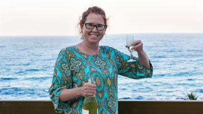 Glad kvinna skålar med vin på en strand.