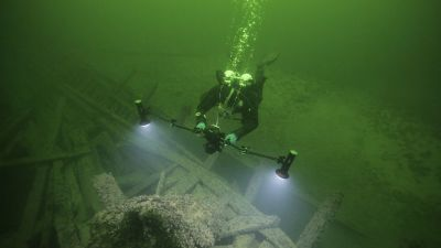 En dykare vid ett vrak på havsbottnen. Dykaren lyser på vraket med en lampa.