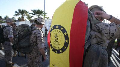 Soldater står med sina ryggsäckar vid en avskedesceremoni i Ceuta den 5 november 2016 inför deras avresa till EU:s krishanteringsoperation i Mali. I närbild en flagga med förkortningen EUTM (European Union Training Mission in Mali).
