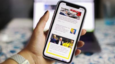 En person håller i en telefon där man kan se Svenska Yles webbplats. I bakgrunden syns en dator.