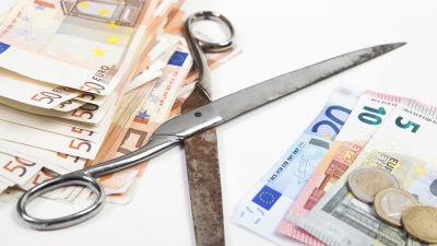 Två högar med eurosedlar och en rostig sax mellan dem.
