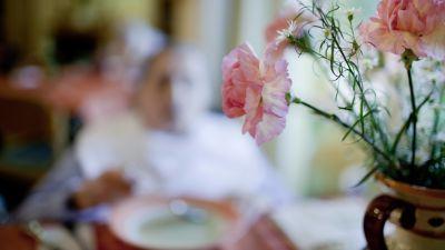 I förgrunden syns en bukett med blommor på ett bord, i bakgrunden syns en äldre kvinna på ett äldre boende som äter soppa.
