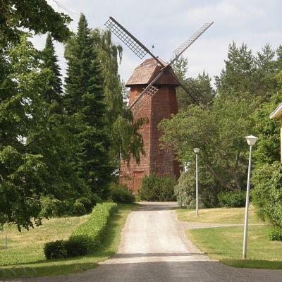 Näkymä Lepaan oppilaitosten pihamaalta kohti Mamselli-tuulimyllyä. Kellarin päällä oleva tiilirakennus pilkottaa tuulimyllyn vasemmalla puolella.