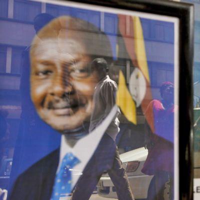 Yoweri Musevenin kuvia näyteikkunassa. Lasista heijastuu ohikulkijoita.