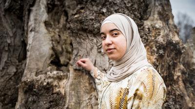 En kvinna poserar framför ett träd. Hon bär slöja och tittar in i kameran.
