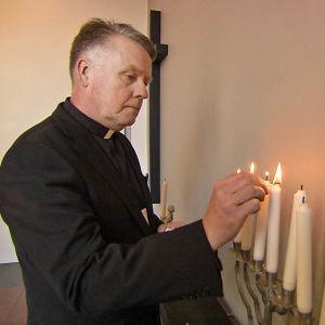 Sairaalateologi Harri sytyttää kynttilöitä lapsipotilaan siunaustilaisuudessa.