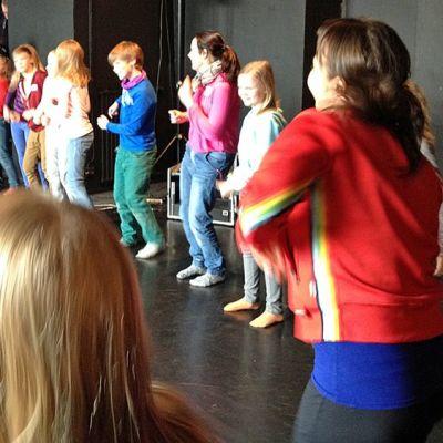 Joukko ihmisiä tanssii ympyrässä.