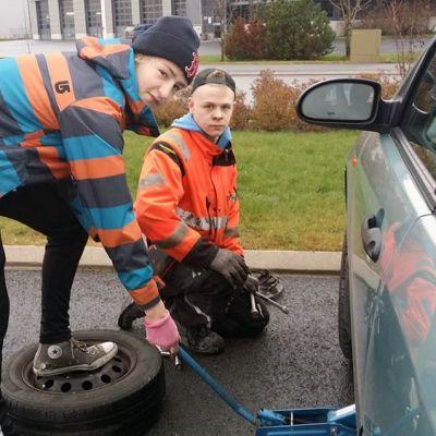 Kaksi lukiolaispoikaa vaihtaa autoon renkaita.