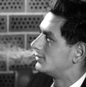 Mies puhaltaa tupakansavua nenästään