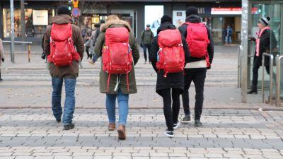fyra personer med röda ryggsäckar går över vägen.