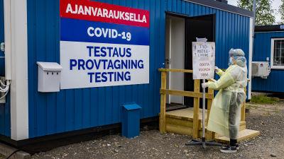 Tornion kaupungin koronatestauksen työntekijä siirtää kylttiä.