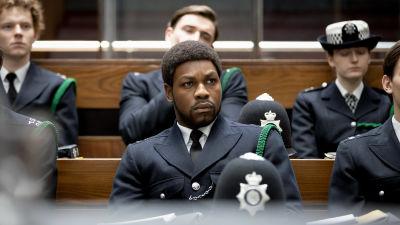 Konstaapeli Leroy Logan (John Boyega) istuu uniformupukuisena muiden poliisien joukossa luentosalissa. Kuva elokuvasta Small Axe: Red, White and Blue