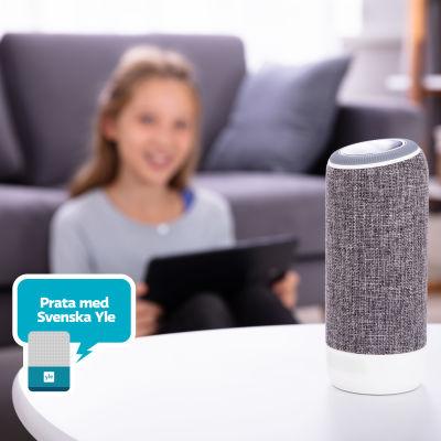Flicka sitter i bakgrunden med pekskärm i handen och talar med en smarthögtalare som står på ett soffbord i förgrunden. På bilden stämpel som säger Prata med Svenska Yle.