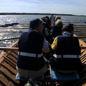 Pyhiinvaeltajat soutavat Pyhän Henrikin saarelle Kirkkokarille vaelluksen toisena päivänä.