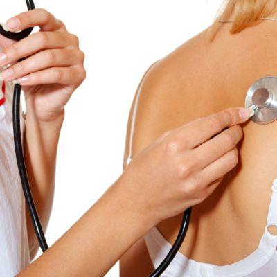 Doktorn checkar lungorna med stetoskop