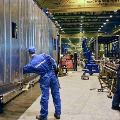 Transtechin työntekijä työntää käsivartensa ratikan kattolevyn sisälle.