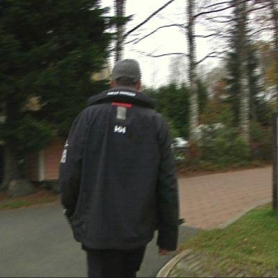Mies kävelemässä pihakatua