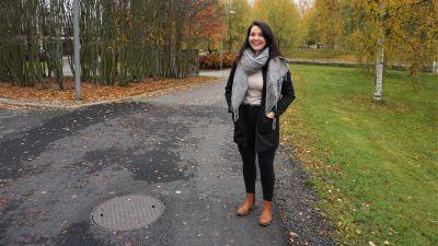 Kvinna i svart jacka står vid kanten av en cykelväg.
