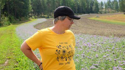 """Forskaren Traci Birge tittar ut på ängen i en gul t-tröja med bilder på olika blommor och texten """"plant these, save the bees""""."""
