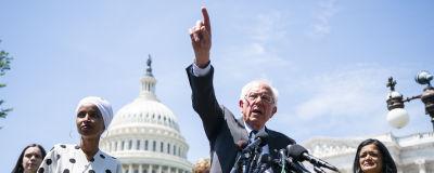 Bernie Sanders framför mikrofoner utanför kongressen med pekfinger i luften.