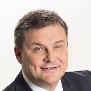 Matti Bergendahl, en man med kavaj, vit skjorta och blå slips.