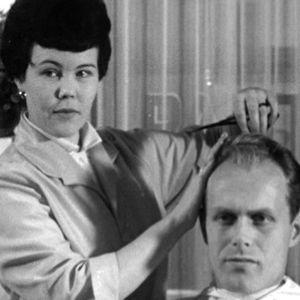 Nainen leikkaa miehen hiuksia