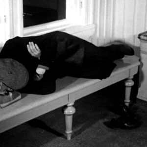Mies nukkuu juna-aseman penkillä