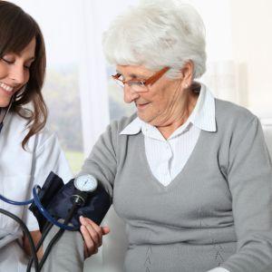 läkare mäter blodtrycket på äldre patient