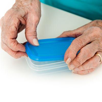 gammal kvinna som öppnar plastburk