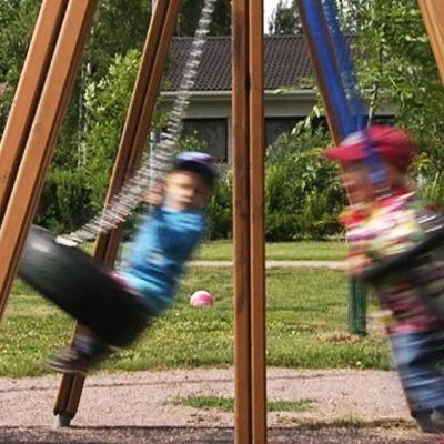 Lapset keinuvat ja vanhemmat antavat vauhtia puistokeinuilla.