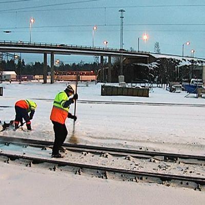 Kaksi miestä harjaa junanraiteita puhtaaksi lumesta.