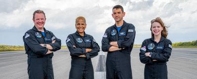 Två kvinnor och två män i svarta astronautdräkter står med armarna i kors och poserar för en kamera på en flygbana utomhus. De ler mot kameran.