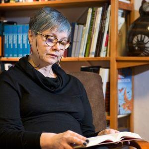 Kirjabloggaaja Erja Metsälä lukee kirjaa nojatuolissa.